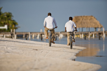Mid-adult man and his son riding bicycles on a sandy beach near the water.