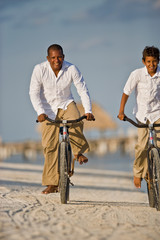 Smiling mid-adult man and his son riding bicycles on a sandy beach.