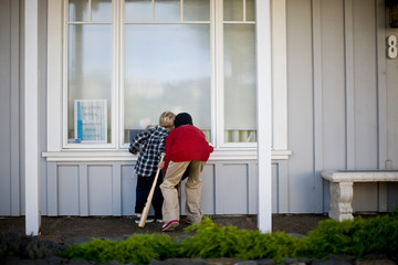 Two boys peering into window of an empty house