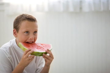 Young boy taking a big bite out of a juicy slice of watermelon.