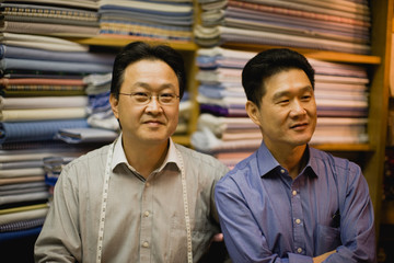 Portrait of two male tailors inside a clothing store.