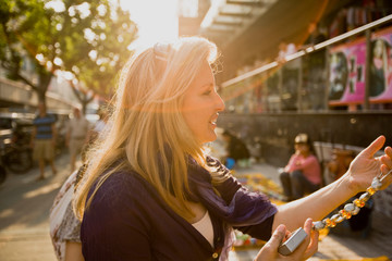 Smiling mid-adult woman holding a beaded necklace while standing in a city street in the sunshine.