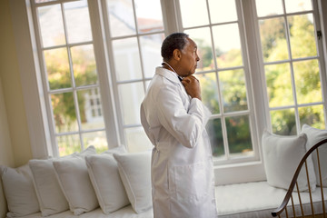 Senior doctor looking thoughtfully out his office windows.