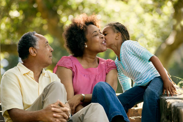 Mature couple sitting with their young granddaughter.