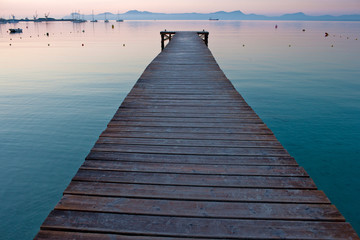Wooden pier and calm sea at sunset.