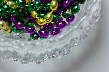 Macro abstract art image of traditional three color Mardi Gras beads in a frosted lead crystal bowl