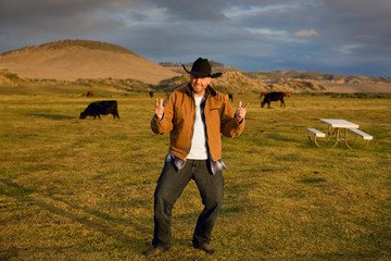 Man in cowboy hat standing in a farm field