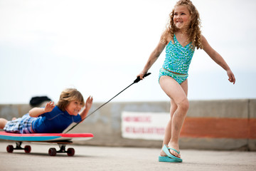Young girl pulling her brother on a makeshift wagon,  made from a boogie board on top of a skateboard.