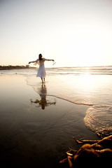 Rear view of a woman in a white dress at the beach,  walking along water's edge at sunset.