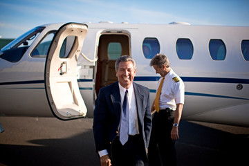 A businessman and a pilot standing in front of a private jet and smiling