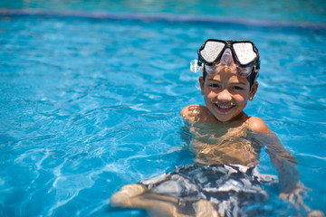 Little boy in pool with snorkel mask on head.