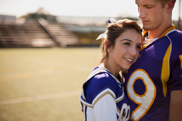 Cheerleader snuggled into football player's chest.