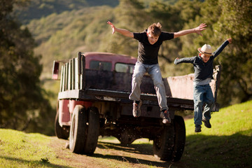 Boys jumping off truck.