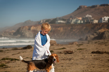 Young boy wrapped in a towel smiles as he stands on the beach with his dog.