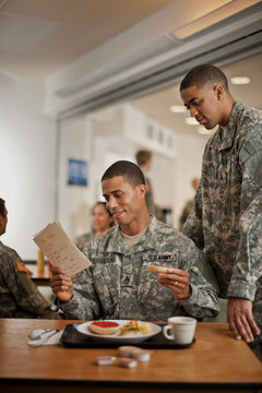Young soldier looks over his friend's shoulder as he reads a  letter during breakfast.