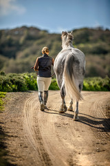 Woman leading her horse on a rural path.
