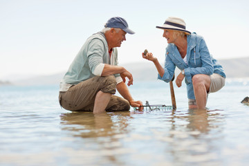 Smiling senior couple collecting rocks on a beach at low tide.