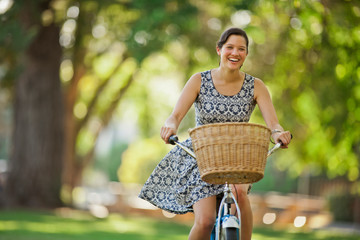 Portrait of a smiling young woman riding her bicycle through a park.