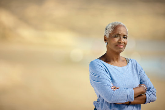 Portrait of a senior woman standing on a beach.