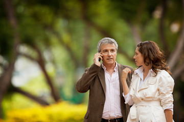 Middle aged man talks on his mobile phone as he walks through a park with his wife.