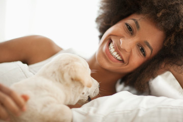 Smiling young woman lying in bed with her Labrador puppy.