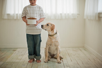 Young boy holding bowl of dog food as his dog looks up at it.
