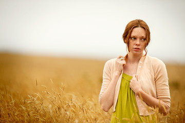 Pensive teenage girl in wheat field.
