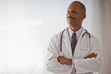 Male doctor with his arms crossed smiling in pride.