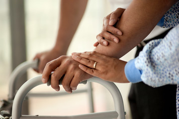 Nurse lays a supporting and comforting hand atop a young male patient's hand as he learns to walk again.