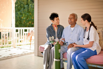 Senior man with nasal tubing sitting on the deck of rest-home with his wife and nurse.