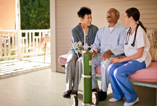 Senior man with nasal tubing sitting on the deck of rest-home and laughing with his wife and nurse.