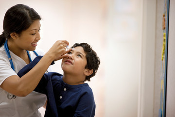 Nurse administering eye drops to a young boy.