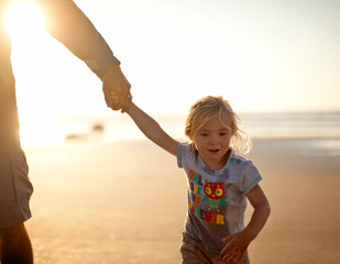 Small girl holding her father's hand at the beach.