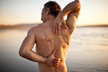 Shirtless man stretching on the beach.