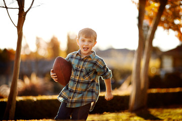 Portrait of running boy holding his rugby ball in the backyard.