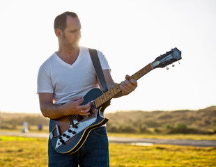 Mid-adult man playing his guitar while standing in a rural field.