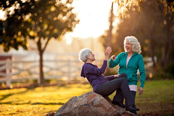 Two smiling senior women giving each other a high-five in a park.
