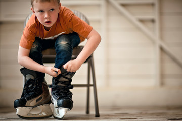 Young boy tying up the laces on his ice skates.