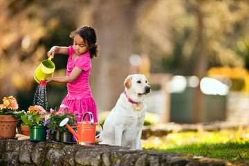 Young girl watering plants in the garden.