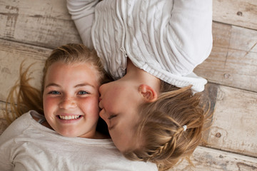 Portrait of a girl being kissed on the cheek by her younger sister while lying on a wooden floor.