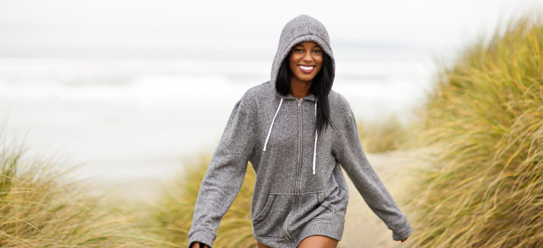 Portrait of a smiling young woman exercising on a beach.