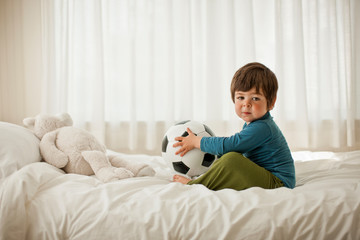Young boy playing on a bed inside a bedroom.