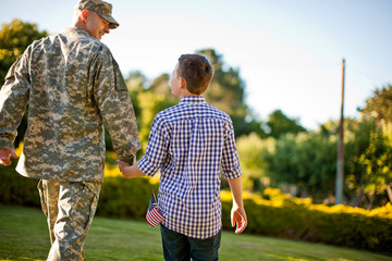 Male soldier holding hands with his son in their back yard.