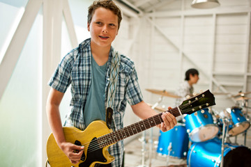 Smiling teenage boy playing an electric guitar while a friend plays the drums inside a garage.