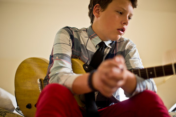 Contemplative teenage boy sitting with his electric guitar.