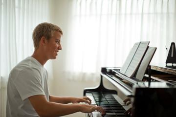 Teenage boy sitting at a piano.