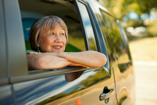 Happy senior woman looking out the window of a SUV.