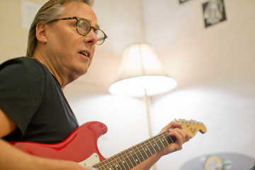 Mature man playing an electric guitar.