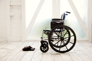 Wheelchair next to a pair of slippers.