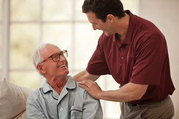 Happy elderly man having a discussion with a male nurse.